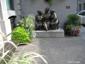 These are three ladies having an interesting conversation.These are statues in front of the building.